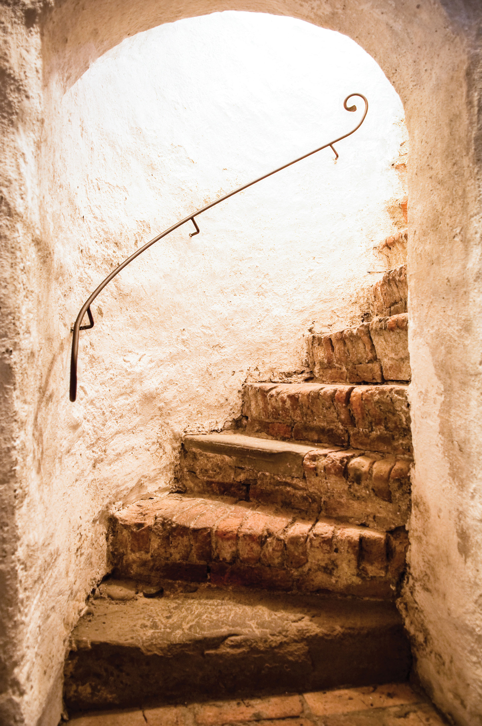 Approaching the top of a Medieval spiral stone staircase, light pouring in