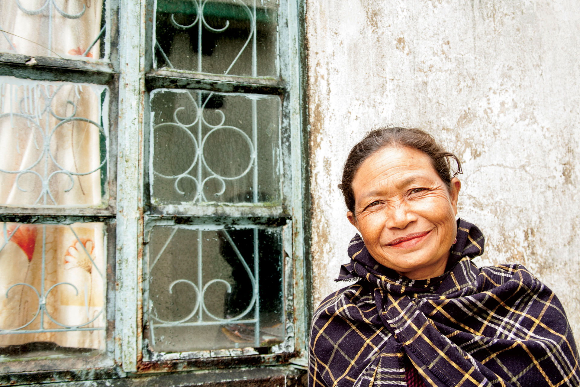 Happy, elderly Nepalese woman in front of house window